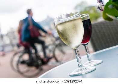 Glasses of white and red wine on a table outside a bar in Amsterdam