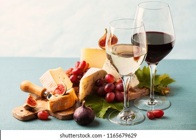 Glasses of white and red wine and variety of cheeses on serving board