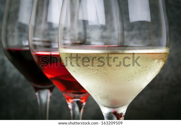 Glasses of white, rose and red wine.  Focus on foreground.