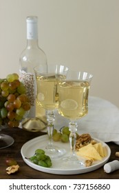 Glasses with white wine and a bottle of wine with a snack - cheese, walnuts and grapes. Rustic style, selective focus.