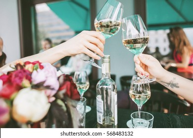 Glasses with white wine in hands making a toast, concept of party