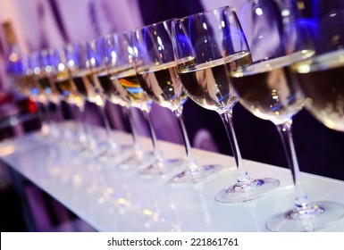 Glasses with white wine lit by festive lights on dark-purple background