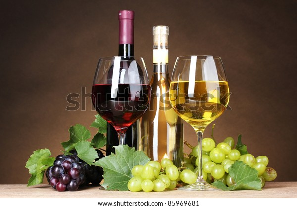 Glasses of wine, bottles and grapes on yellow background