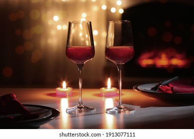 Glasses of wine and candles on table against blurred lights. Romantic dinner