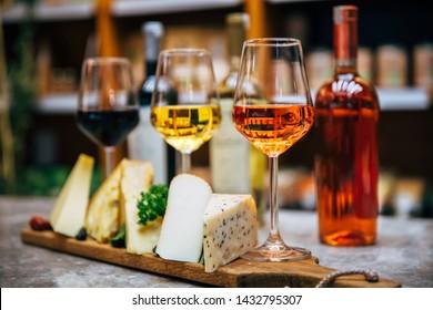 Gläser aus Wein und Käse. Sortiment oder verschiedene Arten von Käse, Weingläser und Flaschen auf dem Tisch im Restaurant. Roter, Rose und gelber Wein oder Champagner auf dem Tisch. Konzept des Weinbaus