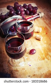 Glasses of wine and grape on texture rusty wooden background