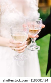 glasses of wine in the hands of the bride and groom