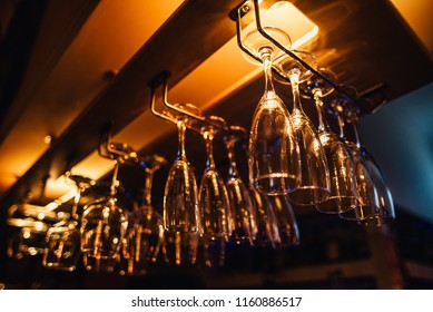 Glasses of wine. Glasses hanging above the bar in the restaurant. Empty glasses for wine. Wine and martini glasses in shelf above a bar rack in restaurant. blue lights, blue background, night life