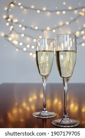 Glasses of wine on glass table with bokeh background close up. New Year, Christmas mood. Greeting card. Party and holiday celebration concept.