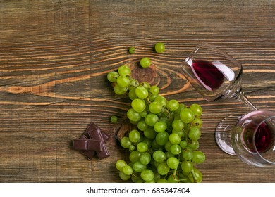 Glasses of wine and ripe grapes isolated on a wooden table