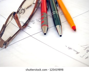 Glasses and writing instruments on a hand written paper