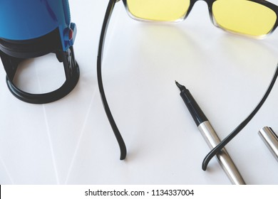 glasses with yellow glasses on a white background and a stamp on the print with a fountain pen, paper background