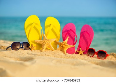 Glasses with yellow and pink sandals stand in the sand against the background of the sea