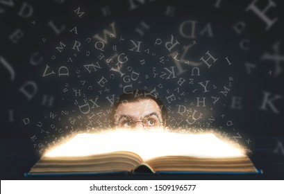 Glasses young man looking up magic letters with magic book in the darkness