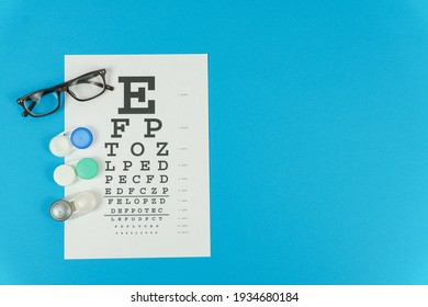 Glasses,lenses and a vision test table on the left on a blue background