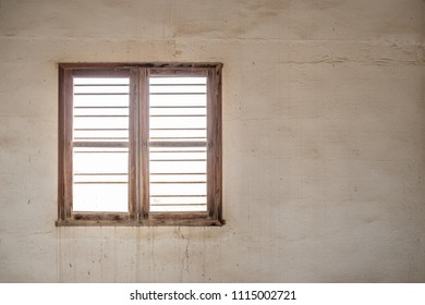 A glassless, barred window in the wall of a room in an abandoned, derelict building with stained walls.