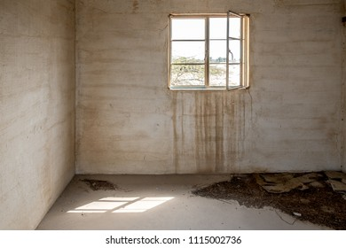 A glassless window stands open in the wall of a room in an abandoned, derelict building with dirt on the floor and stained walls.