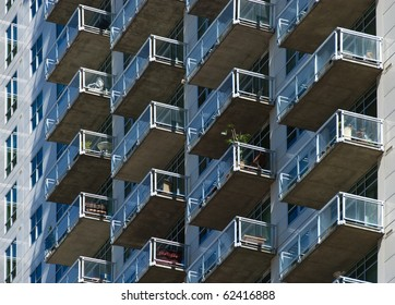 Glass-railing balconies on the side of a tall city skyscraper apartment building.