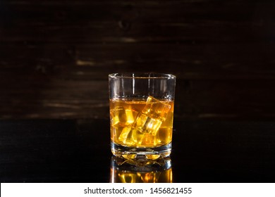 Glasss of whiskey with ice cubes on dark wooden background