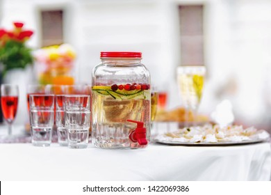 Glassware with colorful drinks on a white table. Close up.