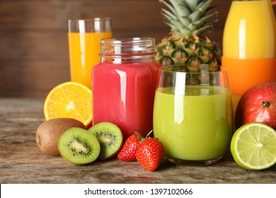 Glassware with different juices and fresh fruits on wooden background