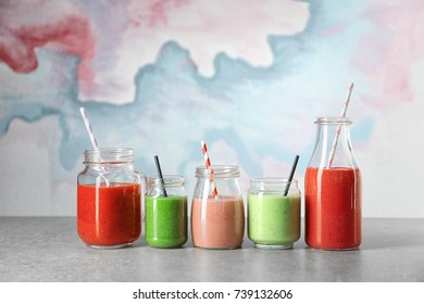 Glassware with different smoothies on table against color background