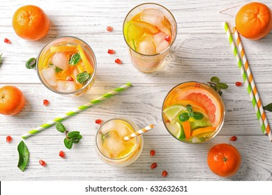 Glassware with refreshing citrus fruits cocktail on white wooden background