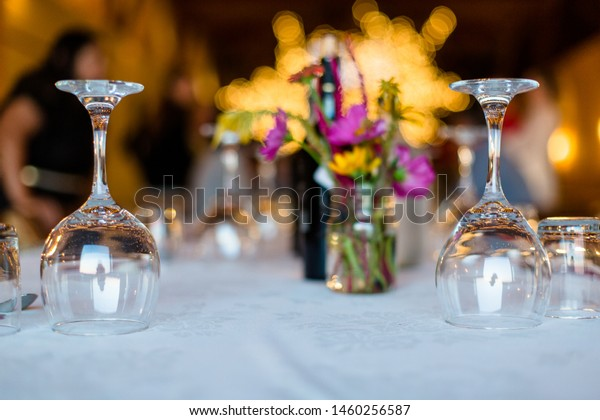 Glassware rests upside down on a white table cloth at the start of a festive dinner party in summer.