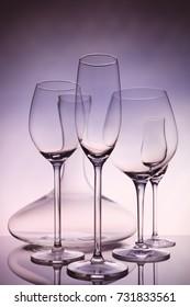 Glassware selection with wine, champagne, liquour glasses and decanter on creative background.. Fine cristal glassware concept. Vertical, warm tone