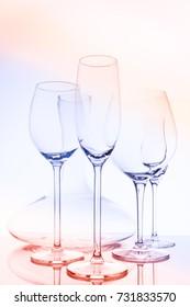 Glassware selection with wine, champagne, liquour glasses and decanter on creative background.. Fine cristal glassware concept. Vertical, triple color tone