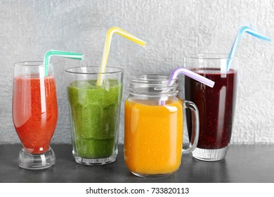 Glassware with smoothies on table against light background