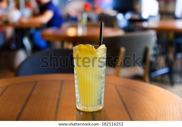 Glassy faceted glass stands on wooden table with black drinking straw, which been poured tea, lemonade, yellow drink with lemon and ginger. Concept of alcoholic and non-alcoholic drinks, waiting for