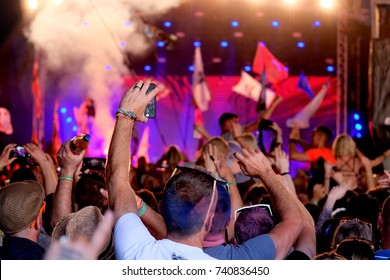 Glastonbury Festival - June 26 2017: Crowd of people from behind with raised arms and flags  waving and enjoying live music at Glastonbury Festival, Pilton, Somerset June 26, 2017 in Somerset, UK