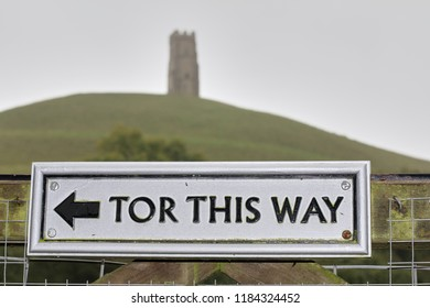 Glastonbury Tor: A sign points visitors towards Glastonbury Tor, a hill near Glastonbury in the English county of Somerset, topped by the roofless St. Michael's Tower.