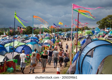 GLASTONBURY, UK - JUNE 27, 2014 : People walking along a path through a camping area at Glastonbury Festival in 2014.
