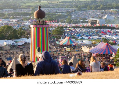 GLASTONBURY, UK - JUNE 28, 2015: Festival-goers on the hill above the Park Stage with views across the entire Glastonbury Festival site, including the Ribbon tower, the Other Stage and Pyramid stage.