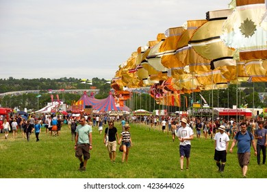 Glastonbury, United Kingdom - June 26, 2014: Crowds enjoy the sunshine at Glastonbury Festival in Somerset, England as they trek across a field beneath brightly colored flags.