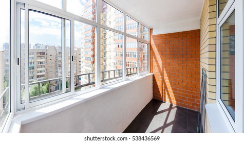 Glazed balcony with brick wall
