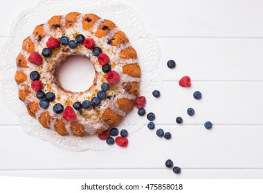 Glazed bundt cake with berries on white table, top view
