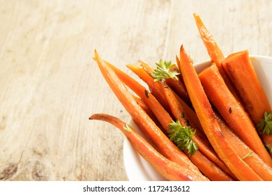 glazed carrot sticks  with parsley garnish in a bowl on a rustic wooden table, corner background with copy space, selected focus, narrow depth of field