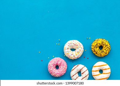 Glazed decorated donuts for sweet break on blue background flat lay copy space