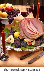 Glazed delicious whole baked honey sliced ham with figs, lemons and champagne grapes.