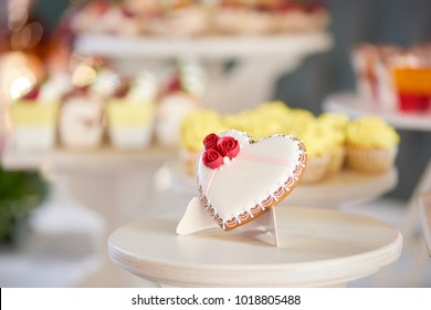 Glazed gingerbread heart stands on the wooden stand in the restaurant. It s decorated with glaze red roses and a little pattern. There is a colorful candybar with cupcakes on the background.