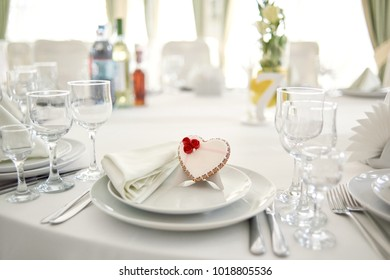 Glazed gingerbread heart stands on a plate in a restaurant. It s decorated with red roses and a little pattern. There are wine glasses and alcohol bottles on the table,covered with white tablecloth.