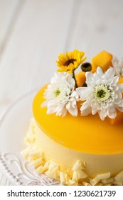 Glazed Mango cheesecake with flowers and fresh mango pieces on grey background , vertical composition, close up