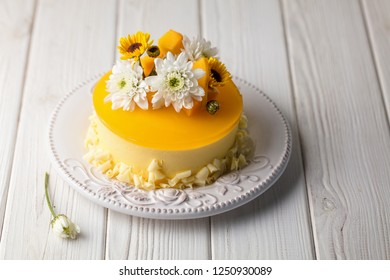 Glazed Mango cheesecake with flowers and fresh mango pieces on white wooden background