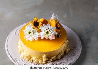 Glazed Mango cheesecake with flowers and fresh mango pieces on round plate on grey background