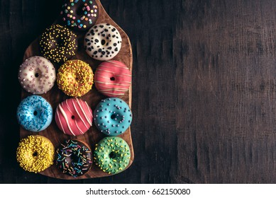 Glazed mini donuts on wooden background with blank space