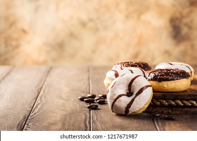 Glazed mini gluten free donuts with coffee candies on wooden background. Party food concept with copy space.