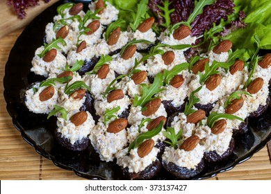 Glazed prunes with cheese, almond and rocket - appetizer